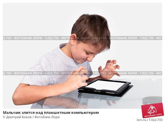 Мальчик злится над планшетным компьютером, фото № 7022733, снято 4 февраля 2015 г. (c) Дмитрий Боков / Фотобанк Лори