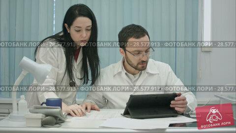 Купить «Male and female doctors discuss medical document», видеоролик № 28577913, снято 24 ноября 2015 г. (c) Vasily Alexandrovich Gronskiy / Фотобанк Лори