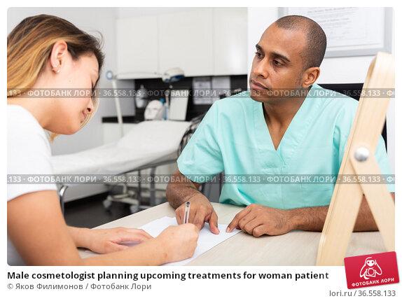 Male cosmetologist planning upcoming treatments for woman patient. Стоковое фото, фотограф Яков Филимонов / Фотобанк Лори