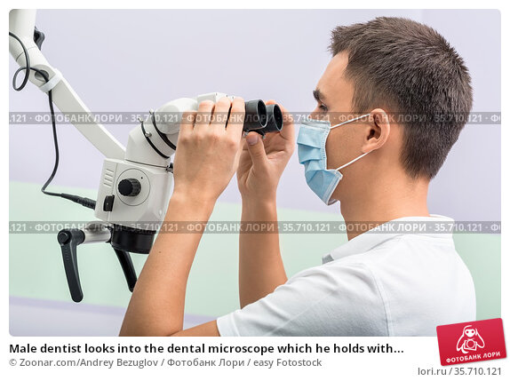 Male dentist looks into the dental microscope which he holds with... Стоковое фото, фотограф Zoonar.com/Andrey Bezuglov / easy Fotostock / Фотобанк Лори