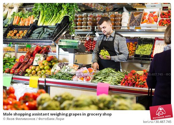 Купить «Male shopping assistant weighing grapes in grocery shop», фото № 30487745, снято 18 марта 2017 г. (c) Яков Филимонов / Фотобанк Лори