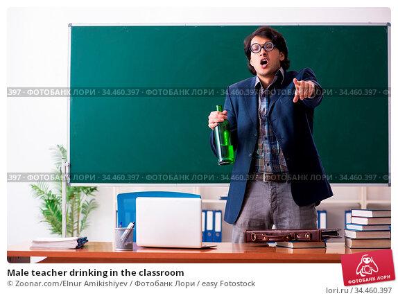 Male teacher drinking in the classroom. Стоковое фото, фотограф Zoonar.com/Elnur Amikishiyev / easy Fotostock / Фотобанк Лори