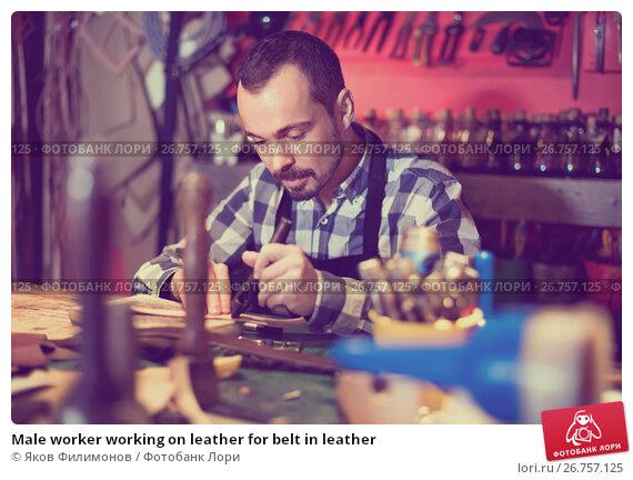 Male worker working on leather for belt in leather, фото № 26757125, снято 26 сентября 2017 г. (c) Яков Филимонов / Фотобанк Лори