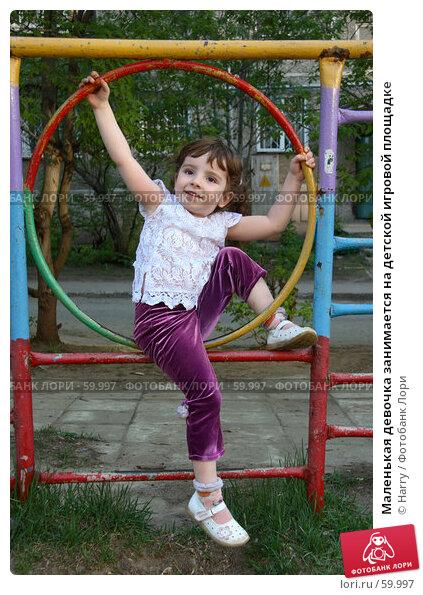 Маленькая девочка занимается на детской игровой площадке, фото № 59997, снято 22 мая 2006 г. (c) Harry / Фотобанк Лори