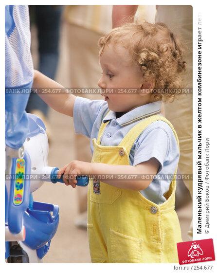 Маленький кудрявый мальчик в желтом комбинезоне играет летним днем в городском парке, фото № 254677, снято 28 мая 2006 г. (c) Дмитрий Боков / Фотобанк Лори