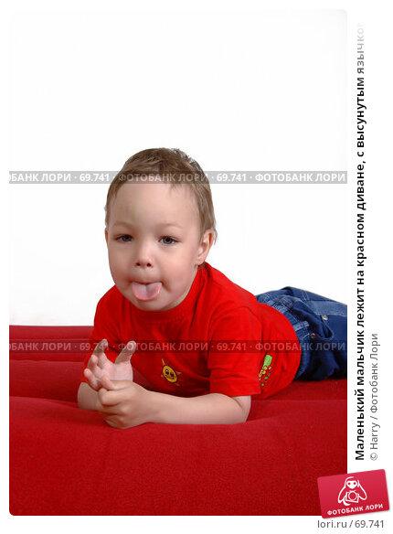 Маленький мальчик лежит на красном диване, с высунутым язычком, фото № 69741, снято 4 июня 2007 г. (c) Harry / Фотобанк Лори