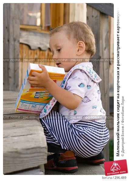 Маленький мальчик сидит на корточках и рассматривает картонную коробку, фото № 296489, снято 16 июля 2006 г. (c) Дмитрий Боков / Фотобанк Лори