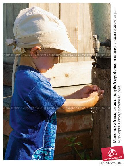 Маленький мальчик в голубой футболке и шапке с козырьком играет с водой около металлического бака с краном летом в деревне, фото № 296485, снято 16 июля 2006 г. (c) Дмитрий Боков / Фотобанк Лори