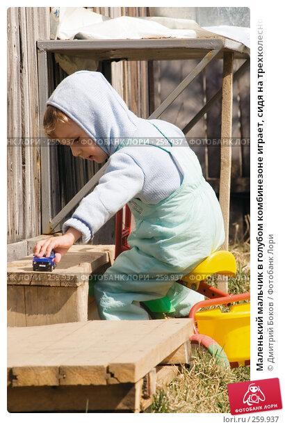 Маленький мальчик в голубом комбинезоне играет, сидя на трехколесном велосипеде, фото № 259937, снято 20 апреля 2008 г. (c) Дмитрий Боков / Фотобанк Лори