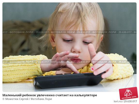 Купить «Маленький ребенок увлеченно считает на калькуляторе», фото № 29630017, снято 30 декабря 2018 г. (c) Момотюк Сергей / Фотобанк Лори