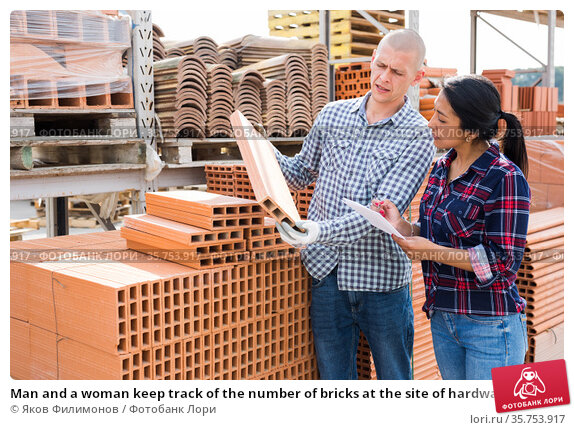 Man and a woman keep track of the number of bricks at the site of hardware store. Стоковое фото, фотограф Яков Филимонов / Фотобанк Лори