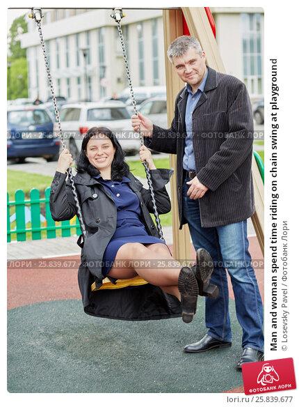 Купить «Man and woman spend time riding on chain swing at playground», фото № 25839677, снято 22 мая 2016 г. (c) Losevsky Pavel / Фотобанк Лори