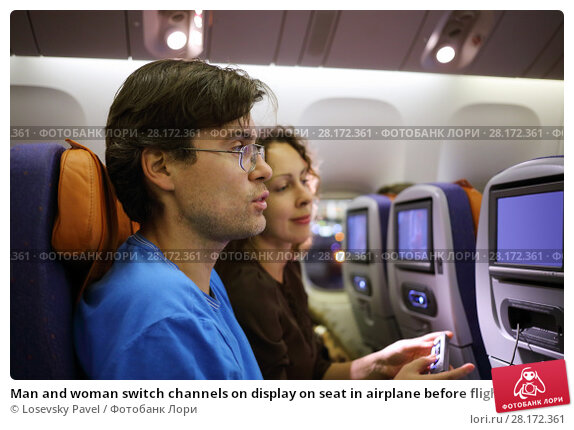 Купить «Man and woman switch channels on display on seat in airplane before flight, focus on man», фото № 28172361, снято 1 ноября 2015 г. (c) Losevsky Pavel / Фотобанк Лори