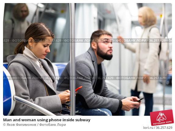 Man and woman using phone inside subway. Стоковое фото, фотограф Яков Филимонов / Фотобанк Лори