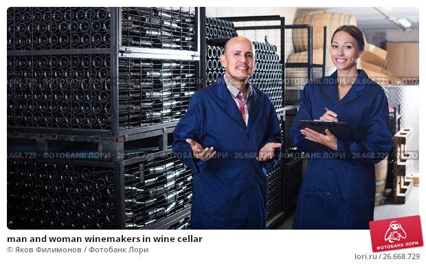 Купить «man and woman winemakers in wine cellar», фото № 26668729, снято 22 мая 2018 г. (c) Яков Филимонов / Фотобанк Лори
