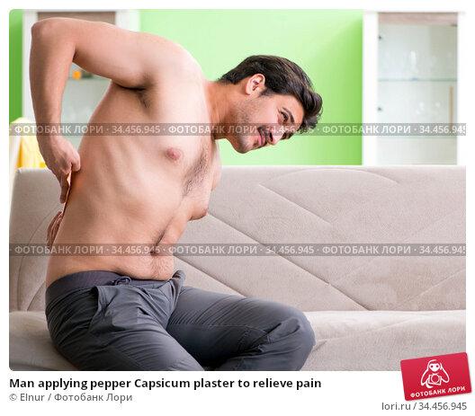 Man applying pepper Capsicum plaster to relieve pain. Стоковое фото, фотограф Elnur / Фотобанк Лори
