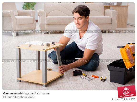 Купить «Man assembling shelf at home», фото № 24249477, снято 27 октября 2016 г. (c) Elnur / Фотобанк Лори