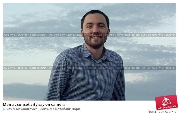 Купить «Man at sunset city say on camera», фото № 28577717, снято 18 января 2019 г. (c) Vasily Alexandrovich Gronskiy / Фотобанк Лори