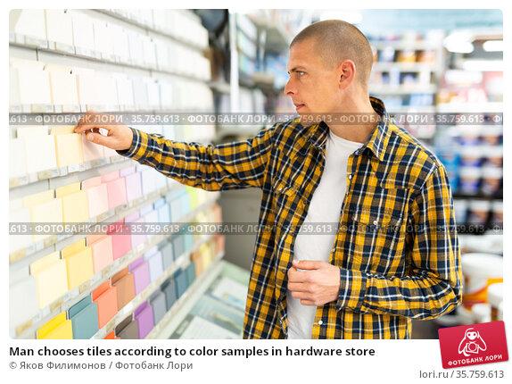 Man chooses tiles according to color samples in hardware store. Стоковое фото, фотограф Яков Филимонов / Фотобанк Лори