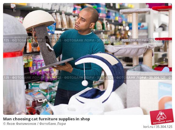 Man choosing cat furniture supplies in shop. Стоковое фото, фотограф Яков Филимонов / Фотобанк Лори