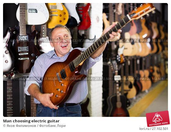 Купить «Man choosing electric guitar», фото № 27102501, снято 18 сентября 2017 г. (c) Яков Филимонов / Фотобанк Лори