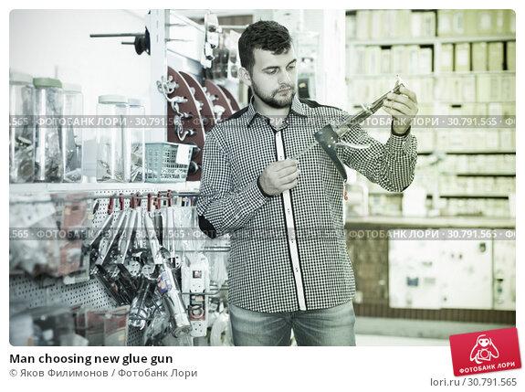 Купить «Man choosing new glue gun», фото № 30791565, снято 5 апреля 2017 г. (c) Яков Филимонов / Фотобанк Лори
