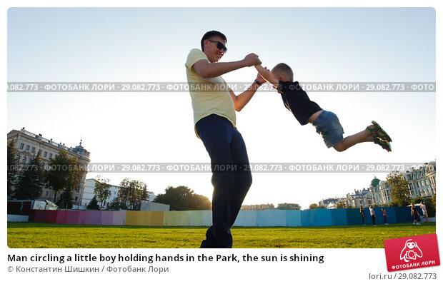 Купить «Man circling a little boy holding hands in the Park, the sun is shining», фото № 29082773, снято 22 сентября 2018 г. (c) Константин Шишкин / Фотобанк Лори