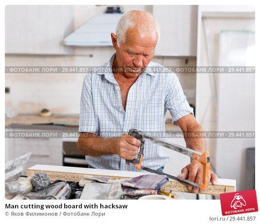 Купить «Man cutting wood board with hacksaw», фото № 29441857, снято 19 июня 2018 г. (c) Яков Филимонов / Фотобанк Лори