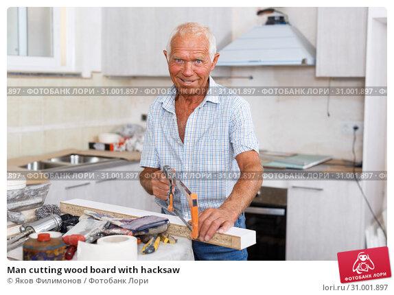 Купить «Man cutting wood board with hacksaw», фото № 31001897, снято 19 июня 2018 г. (c) Яков Филимонов / Фотобанк Лори