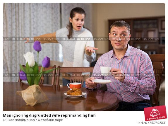 Man ignoring disgruntled wife reprimanding him. Стоковое фото, фотограф Яков Филимонов / Фотобанк Лори