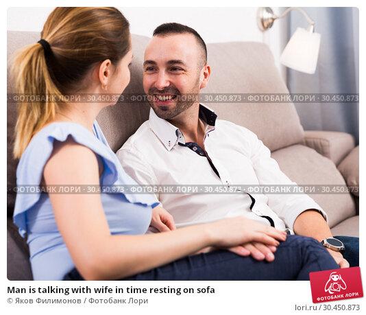 Man is talking with wife in time resting on sofa. Стоковое фото, фотограф Яков Филимонов / Фотобанк Лори