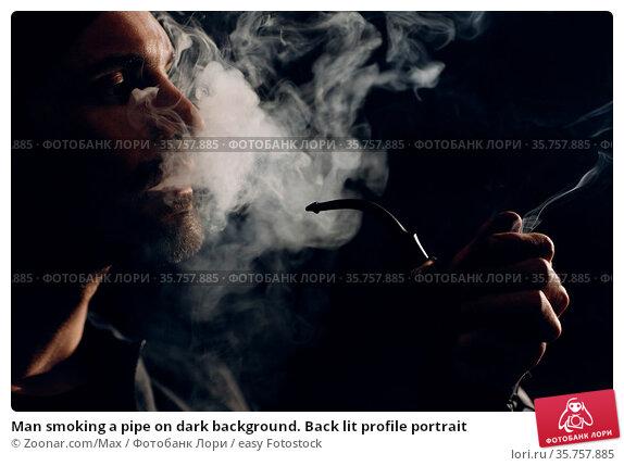 Man smoking a pipe on dark background. Back lit profile portrait. Стоковое фото, фотограф Zoonar.com/Max / easy Fotostock / Фотобанк Лори