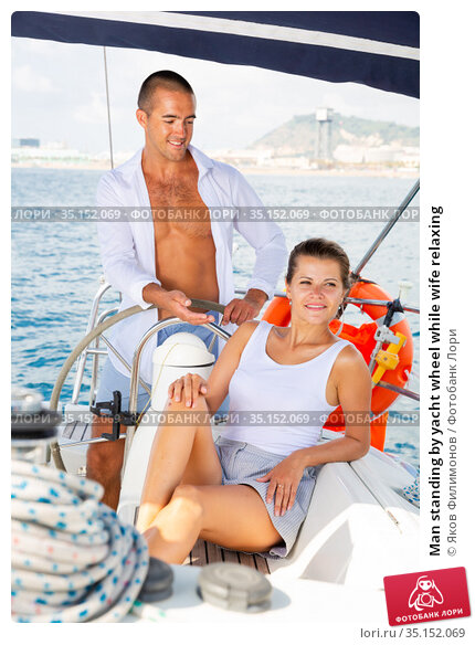 Man standing by yacht wheel while wife relaxing. Стоковое фото, фотограф Яков Филимонов / Фотобанк Лори