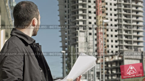 Купить «Man with documentation near construction of a new building», видеоролик № 28574893, снято 11 октября 2015 г. (c) Vasily Alexandrovich Gronskiy / Фотобанк Лори