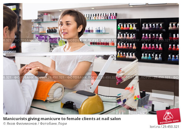 Купить «Manicurists giving manicure to female clients at nail salon», фото № 29450321, снято 28 апреля 2017 г. (c) Яков Филимонов / Фотобанк Лори