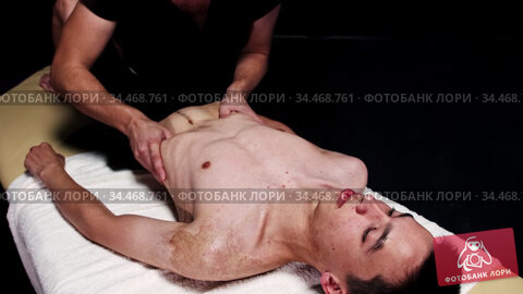 Massage session in dark studio - therapist pushing on the stomach and ribs of his client. Стоковое видео, видеограф Константин Шишкин / Фотобанк Лори