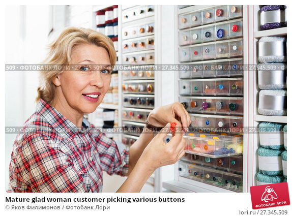 Купить «Mature glad woman customer picking various buttons», фото № 27345509, снято 27 мая 2019 г. (c) Яков Филимонов / Фотобанк Лори