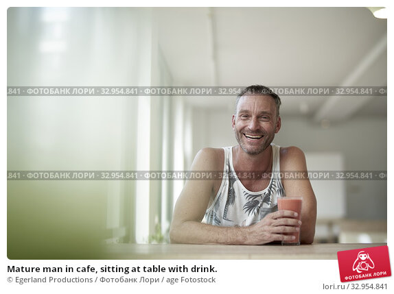 Mature man in cafe, sitting at table with drink. Стоковое фото, фотограф Egerland Productions / age Fotostock / Фотобанк Лори