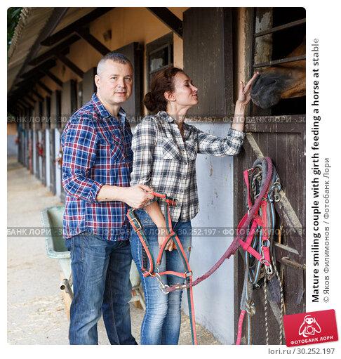 Купить «Mature smiling couple with girth feeding a horse at stable», фото № 30252197, снято 4 июля 2018 г. (c) Яков Филимонов / Фотобанк Лори