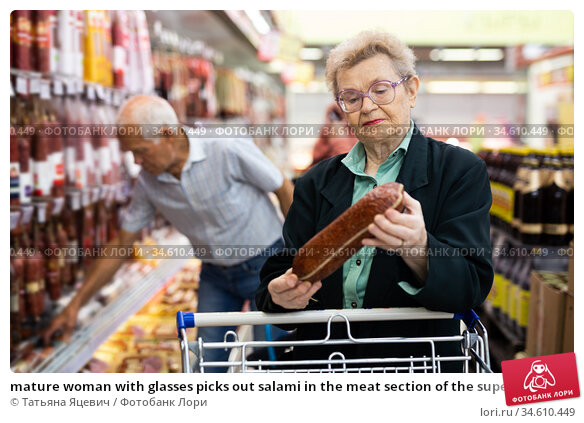 mature woman with glasses picks out salami in the meat section of the supermarket. Стоковое фото, фотограф Татьяна Яцевич / Фотобанк Лори
