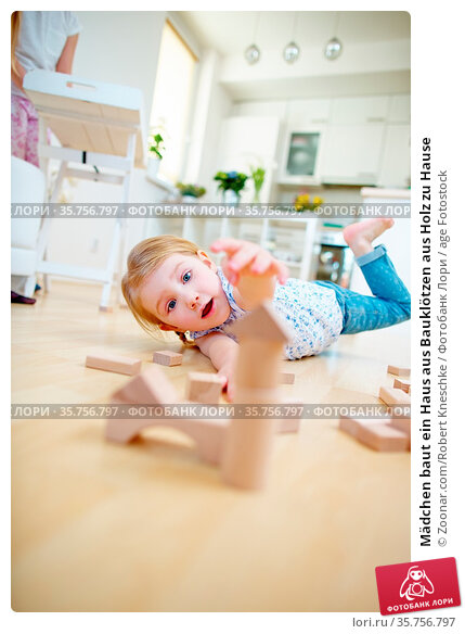 Mädchen baut ein Haus aus Bauklötzen aus Holz zu Hause. Стоковое фото, фотограф Zoonar.com/Robert Kneschke / age Fotostock / Фотобанк Лори