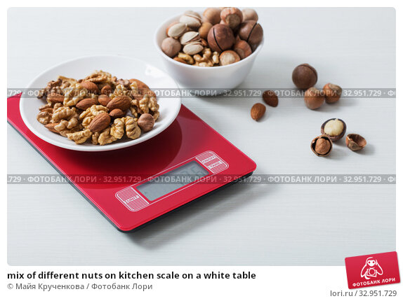 mix of different nuts on kitchen scale on a white table. Стоковое фото, фотограф Майя Крученкова / Фотобанк Лори