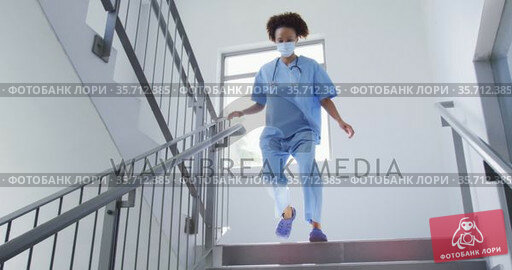 Mixed race female doctor wearing face mask running down stairs in hospital. Стоковое видео, агентство Wavebreak Media / Фотобанк Лори