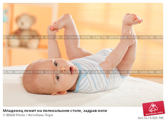 Купить «Младенец лежит на пеленальном столе, задрав ноги», фото № 5925745, снято 16 июня 2019 г. (c) BE&W Photo / Фотобанк Лори