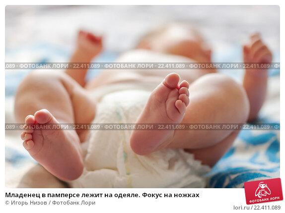 Купить «Младенец в памперсе лежит на одеяле. Фокус на ножках», эксклюзивное фото № 22411089, снято 6 мая 2015 г. (c) Игорь Низов / Фотобанк Лори