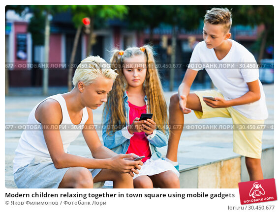 Modern children relaxing together in town square using mobile gadgets. Стоковое фото, фотограф Яков Филимонов / Фотобанк Лори