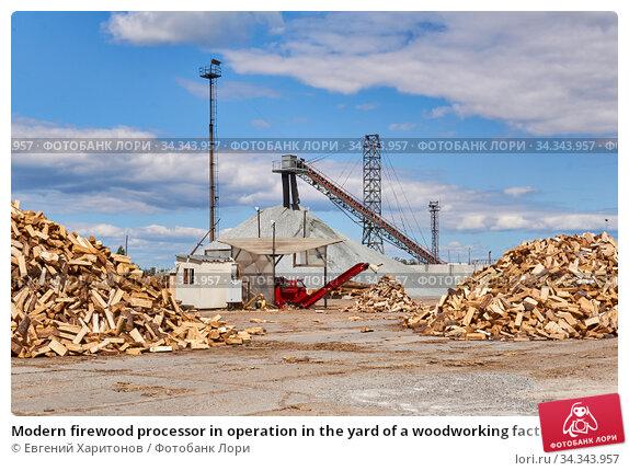 Modern firewood processor in operation in the yard of a woodworking factory. Стоковое фото, фотограф Евгений Харитонов / Фотобанк Лори