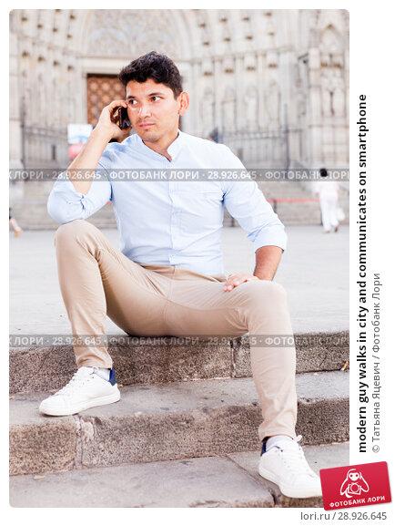 Купить «modern guy walks in city and communicates on smartphone», фото № 28926645, снято 25 июля 2018 г. (c) Татьяна Яцевич / Фотобанк Лори
