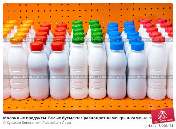 Купить «Молочные продукты. Белые бутылки с разноцветными крышками на полке магазина», фото № 13006161, снято 9 мая 2012 г. (c) Куликов Константин / Фотобанк Лори