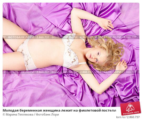 Молодая беременная женщина лежит на фиолетовой постели. Стоковое фото, фотограф Марина Теплякова / Фотобанк Лори